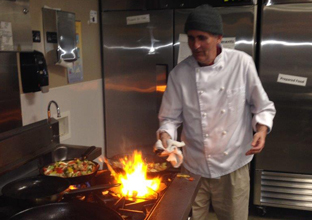 Bill demonstrates his chef skills in the kitchen at Create Common Ground