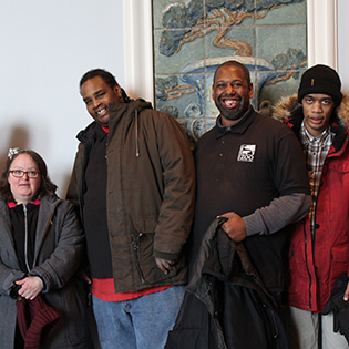 Diverse group of adults with disabilties stand smiling in front of ornate wall of Rookwood tiles.