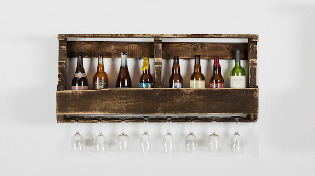 wine rack made of old wooden pallet, filled with wine bottles and with wine glasses hanging below