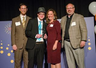 Chairperson Dov Rosenberg, CEO Pam Green, and Board Member Greg Hammond present the Upward Mobility Award in 2017 to Nathan Johnson..