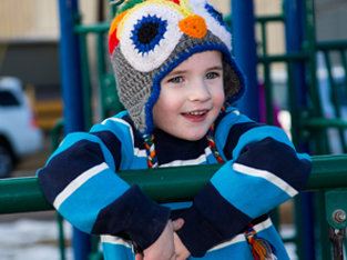 Elijah smiling as he plays on playground equipment