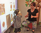 Child using interactive Promethean Board with teacher