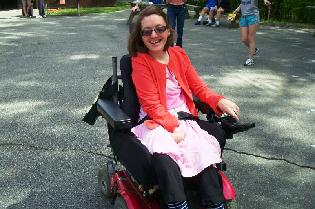 Young smiling girl in wheelchair crossing Walk finish line
