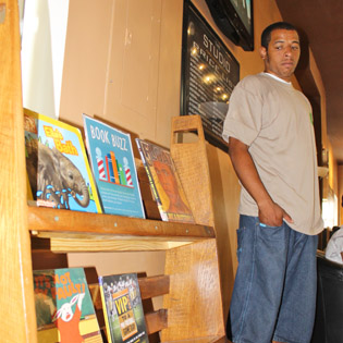 Building Ability constructs bookcases with wood from Building Value to shelve children's books at barbershops