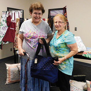 Sewing teacher and class participant hold a purse