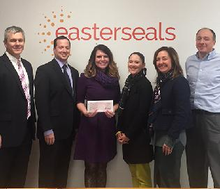 A group of six professionals standing in front of the Easterseals logo, smiling. One woman in the center displays the gift check.