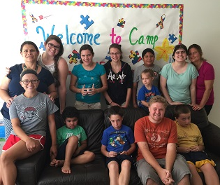Lily Academy Students & Teachers in front of camp sign