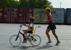 Child riding bike with a volunteer supervisor