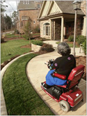 Woman in a scooter entering an accessible home
