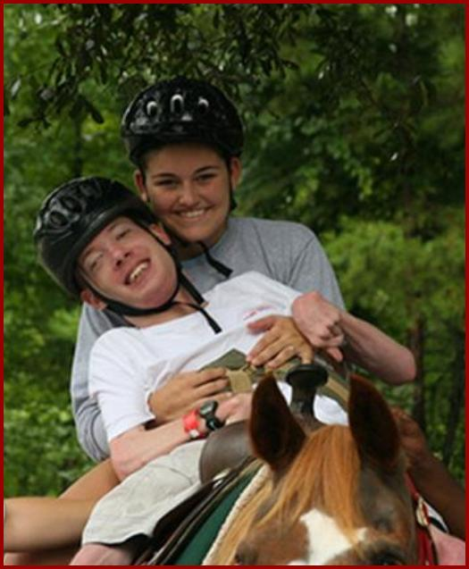 Camper riding a horse with a counselor